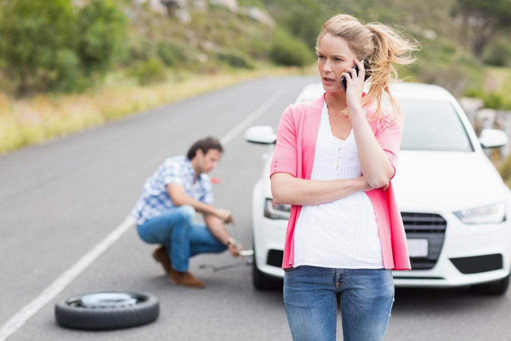 man is changing tire woman trying to contact someone
