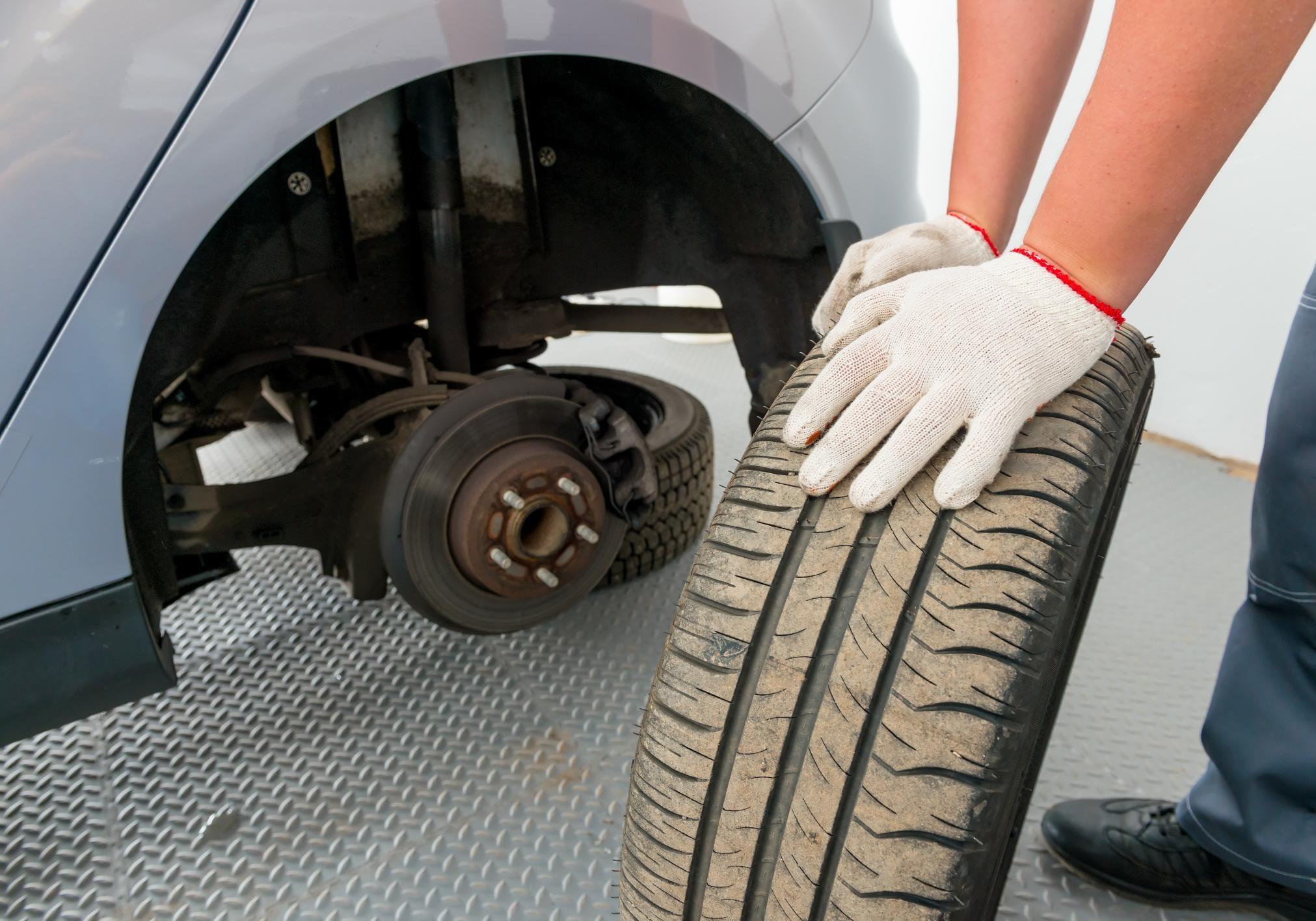 car technician is changing flat tires